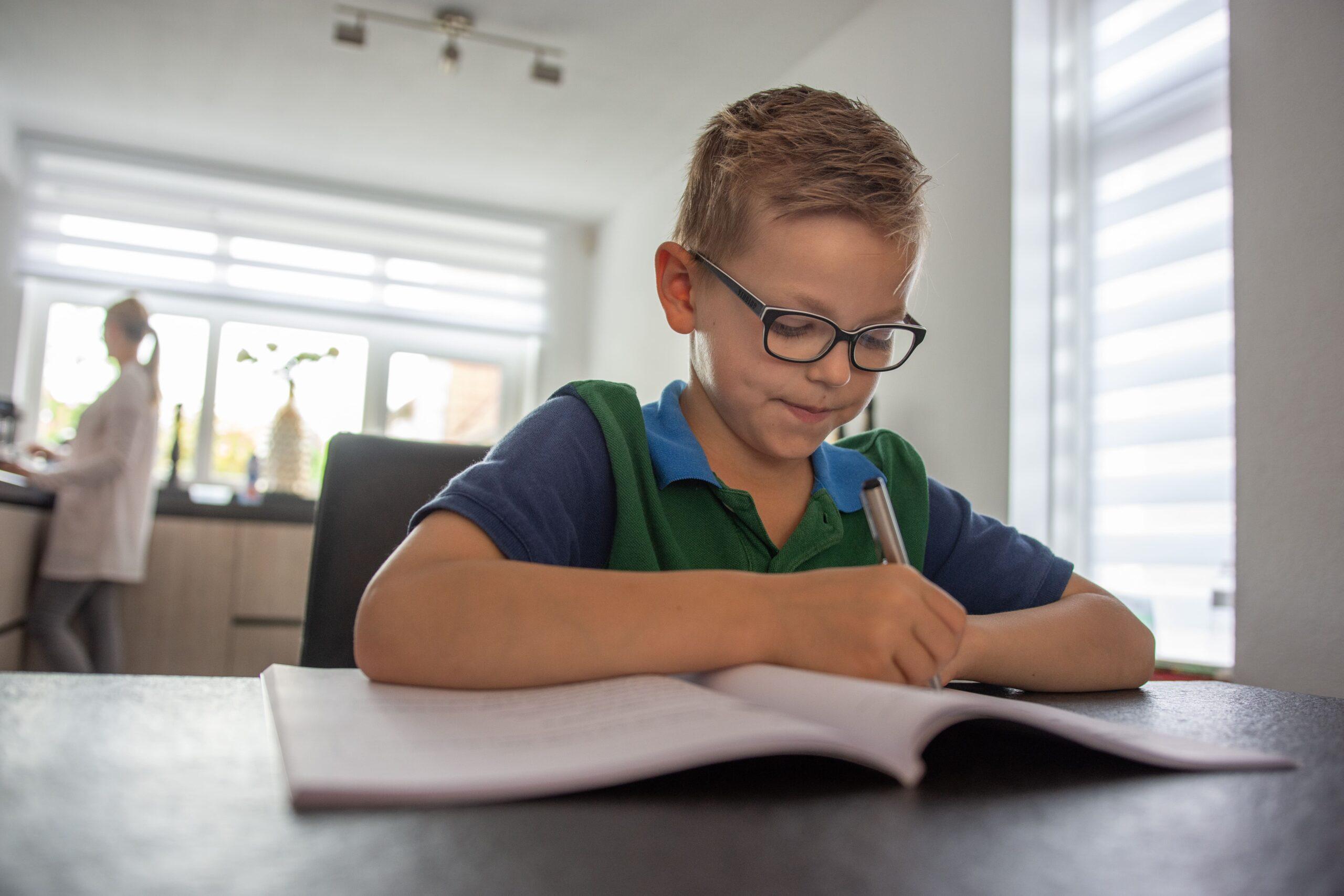 jongetje schrijft in schrift