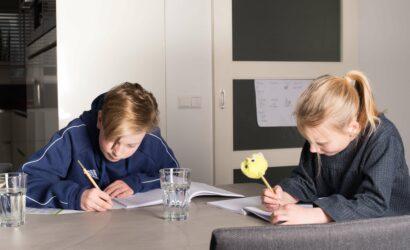 Kinderen maken huiswerk aan eettafel