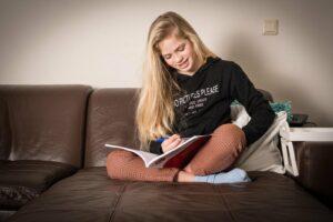 Meisje op de bank huiswerk maken