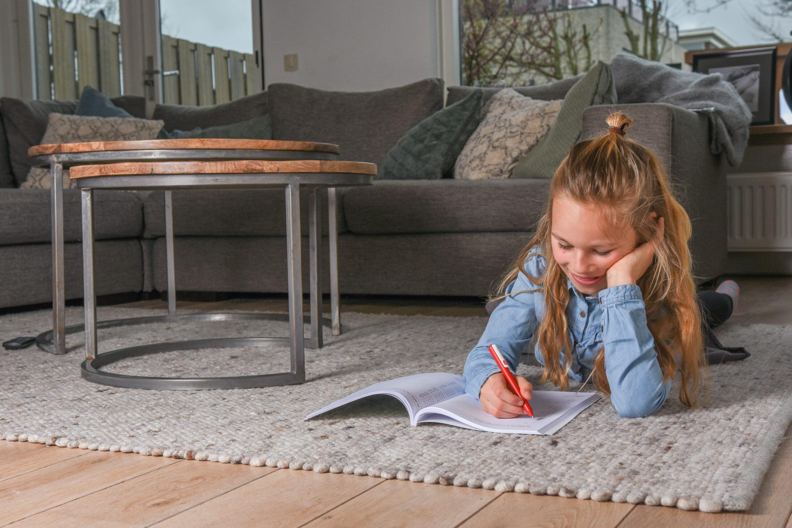 Meisje schrijft op de grond in boek
