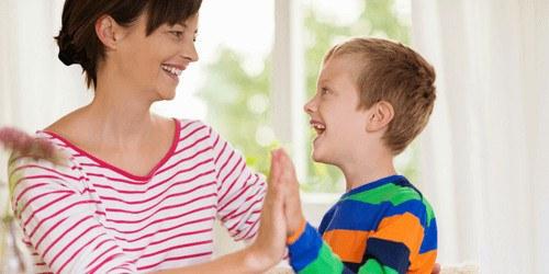 jongetje en moeder geven high five