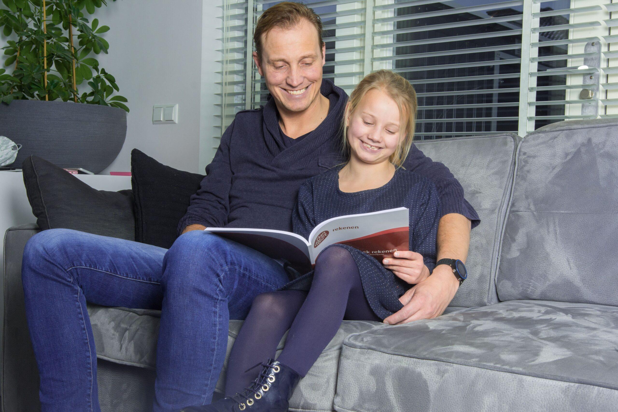 vader en dochter met oefenboek op de bank