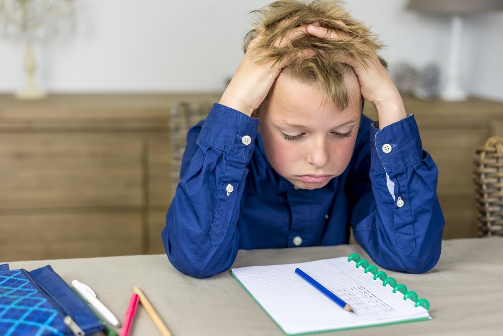 jongetje heeft stress bij huiswerk maken