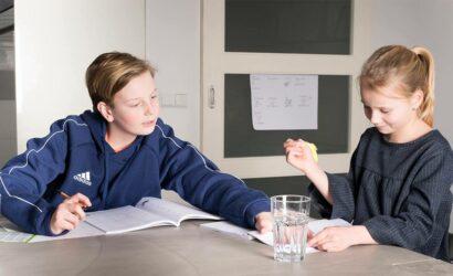 jongen en meisje aan tafel met werkboek