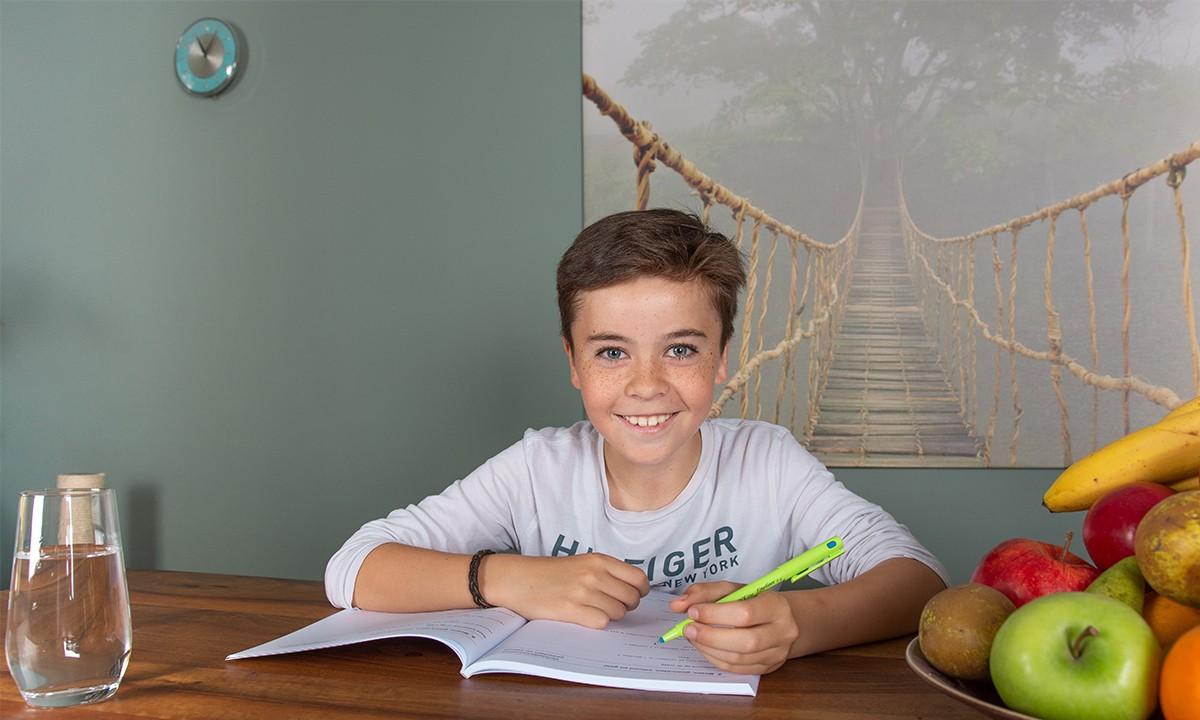 jongen schrijven in oefenboek