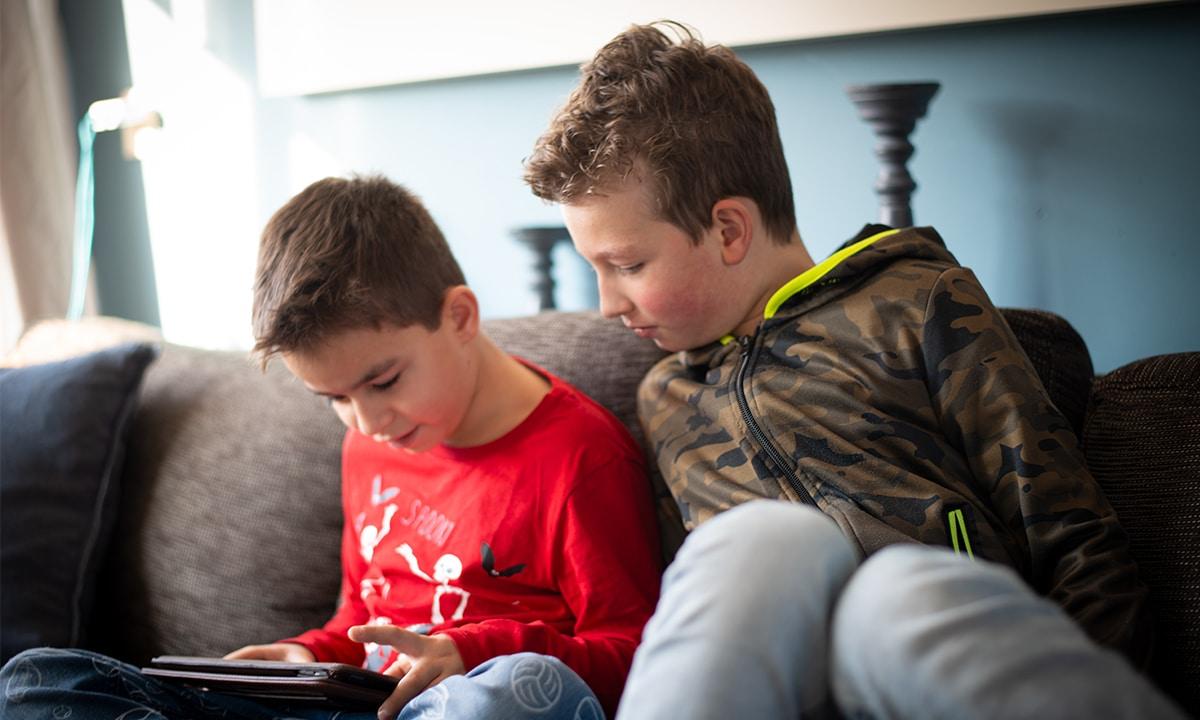 twee jongens op bank met ipad