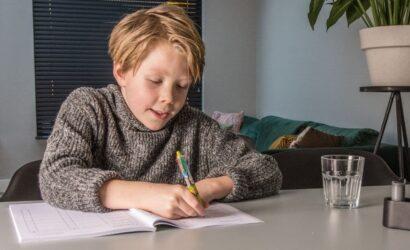 jongen schrijft in boek