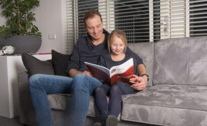 vader dochter op de bank met werkboek rekenen