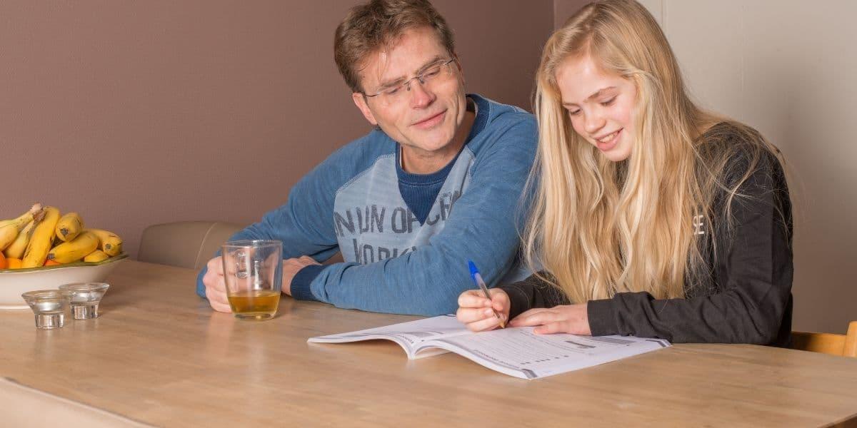 vader en dochter oefenen aan de tafel