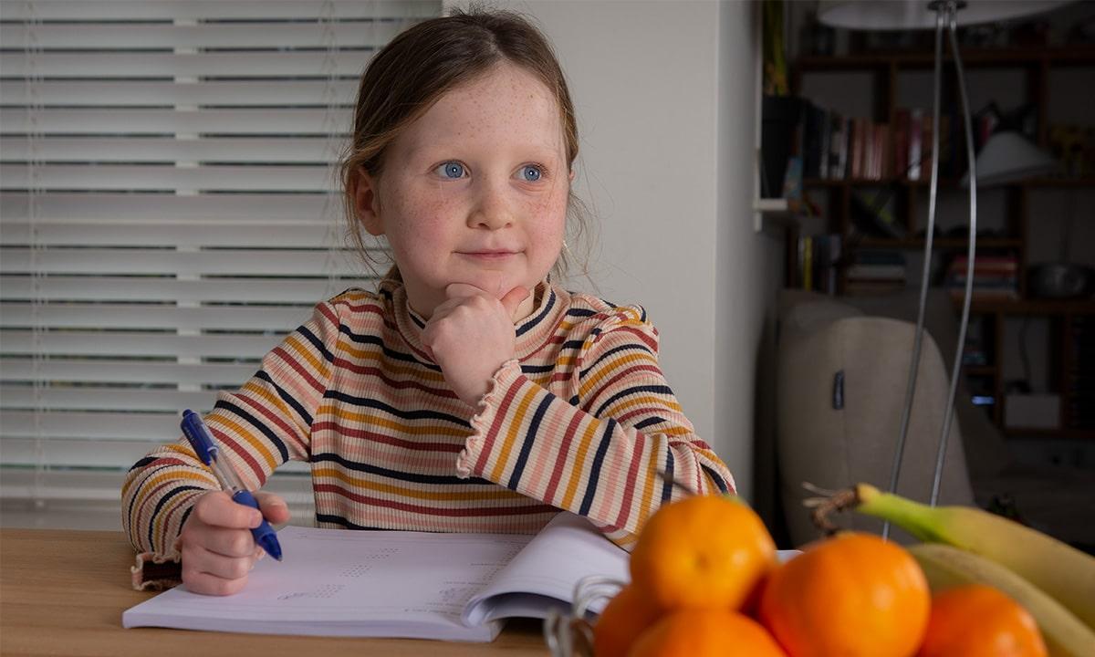 Meisje denkt na over opdracht in werkboek