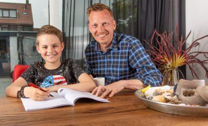 vader helpt zoon met huiswerk