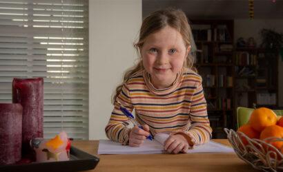 Meisje aan tafel met pen en werkboek