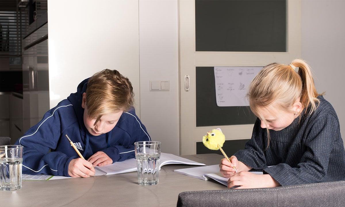 broer en zus maken schoolopdrachten aan tafel