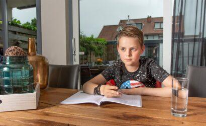 jongen aan tafel met werkboek