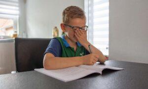jongen met werkschrift aan tafel hand voor mond