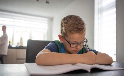 jongetje maakt school opdrachten in de keuken