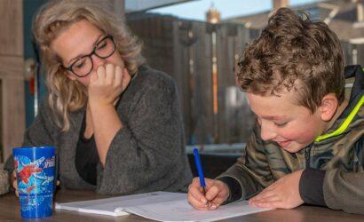 moeder helpt zoon met oefeningen in werkboek