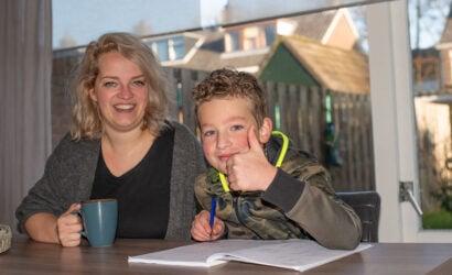 moeder helpt zoon met schoolopdrachten aan tafel
