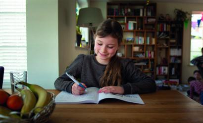 meisje maakt huiswerk aan keukentafel