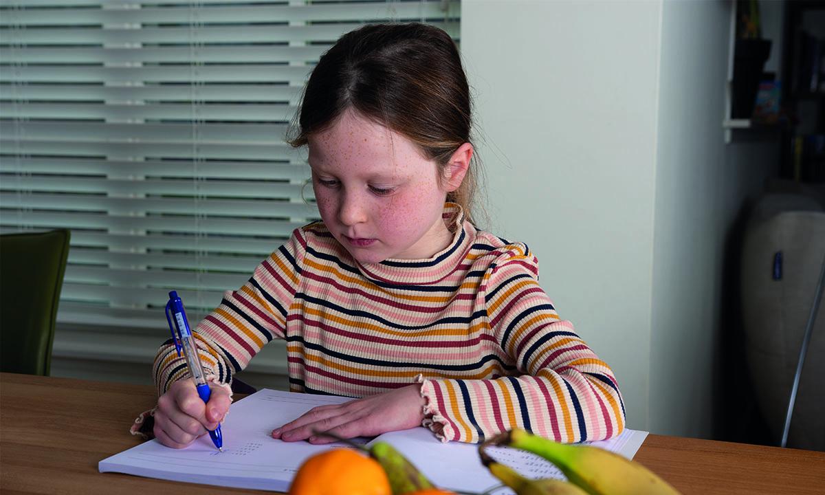meisje maakt oefenopdrachten in boek
