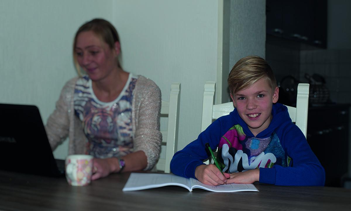 moeder en zoon werken aan tafel aan schoolopdrachten