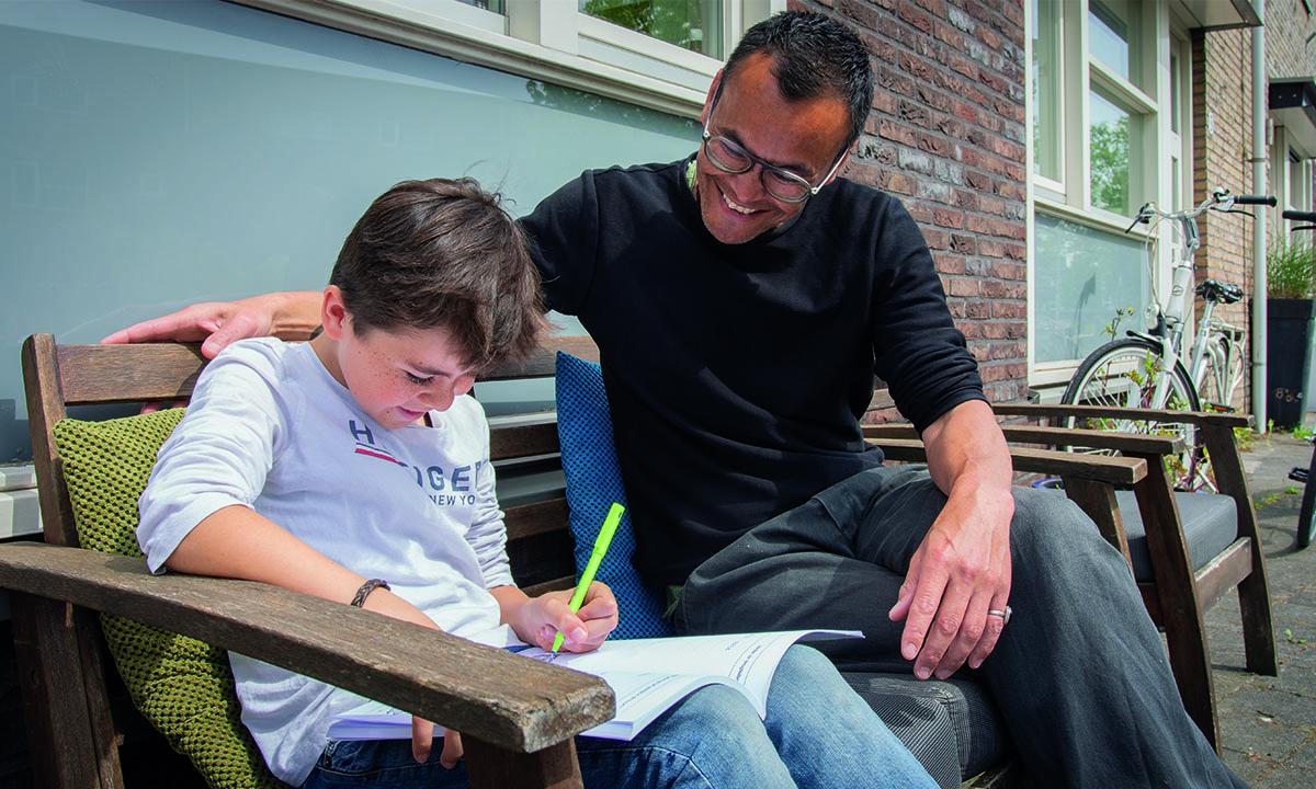 jongen en vader zitten buiten in de zon op een bankje en maken huiswerk