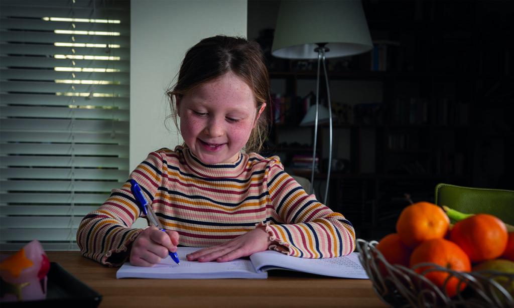meisje aan tafel met pen in hand maakt opdrachten