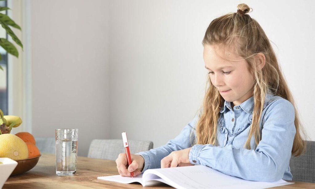 meisje ijverig aan het werk in werkboek aan tafel
