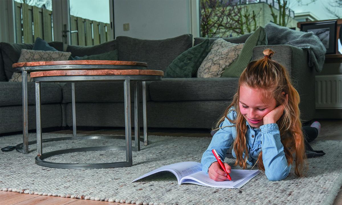meisje op vloerkleed maakt huiswerk