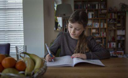 meisje zit aan tafel met werkboek