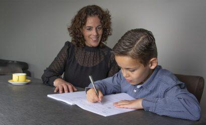 moeder en zoon aan tafel schrijven in oefenboek