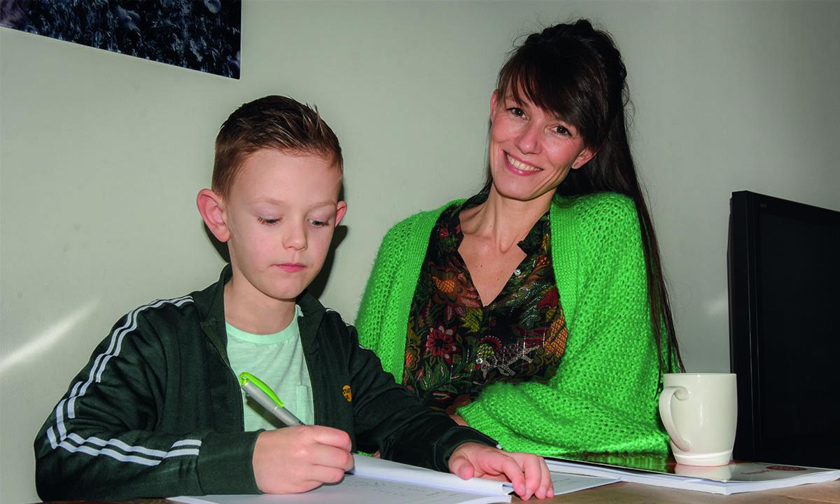 moeder en zoon maken samen opdrachten uit een werkboek