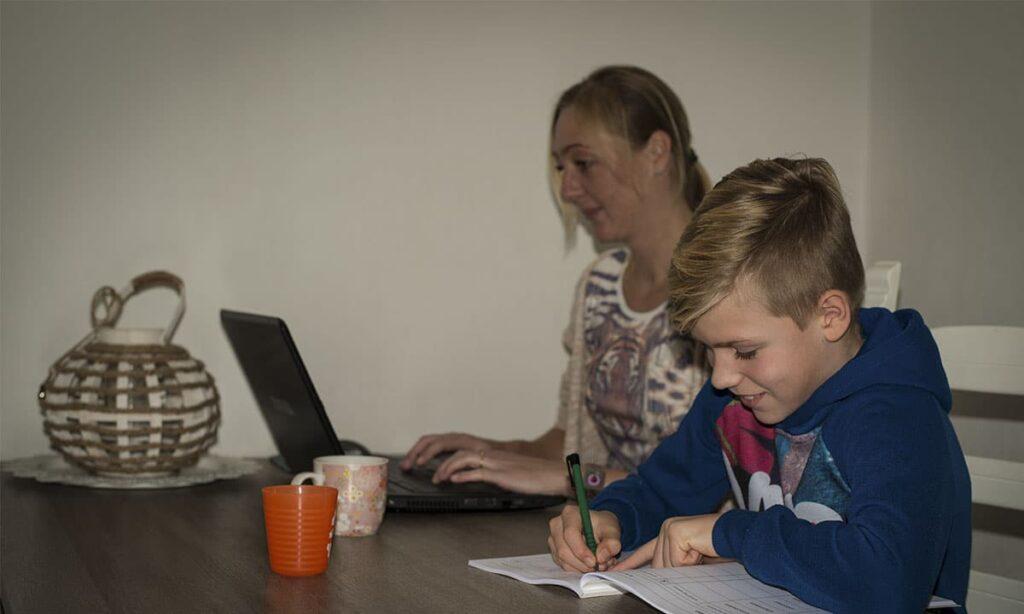 moeder werkt aan laptop en zoon maakt opdrachten in werkboek