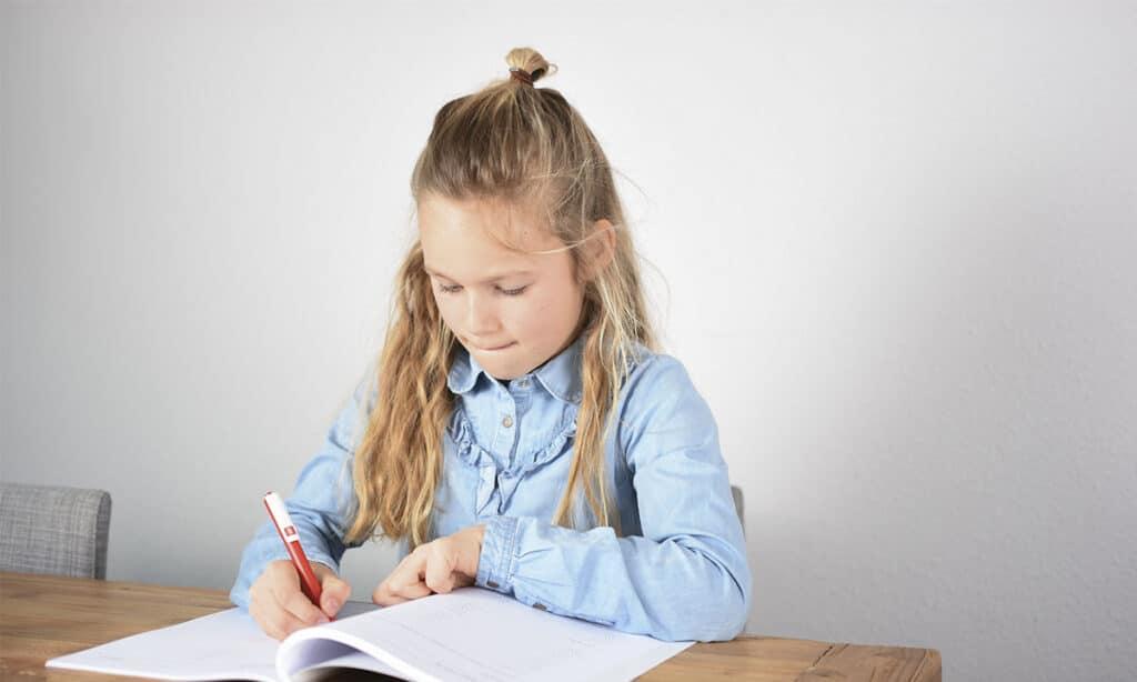 meisje werkt geconcentreerd in werkboek