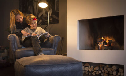 moeder en zoon in fauteuil voor de open haard leren uit werkboek