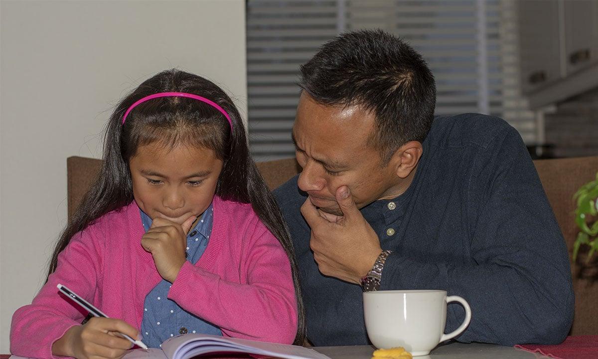 vader helpt dochter met oefenopdrachten