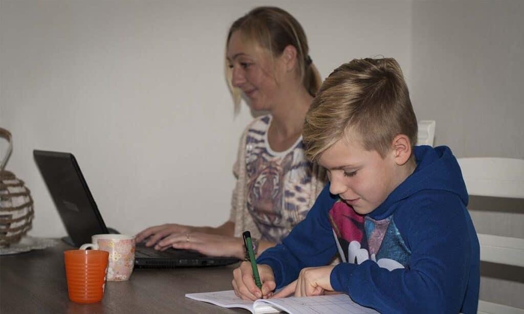 moeder en zoon werken samen aan de keukentafel