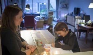 moeder helpt kind met oefeningen uit een werkboek