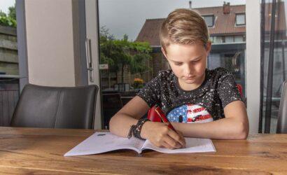 jongen maakt opdrachten aan tafel in werkboek