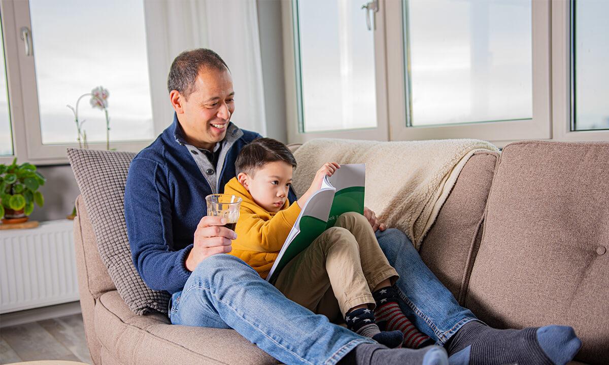 vader en zoon lezen op de bank