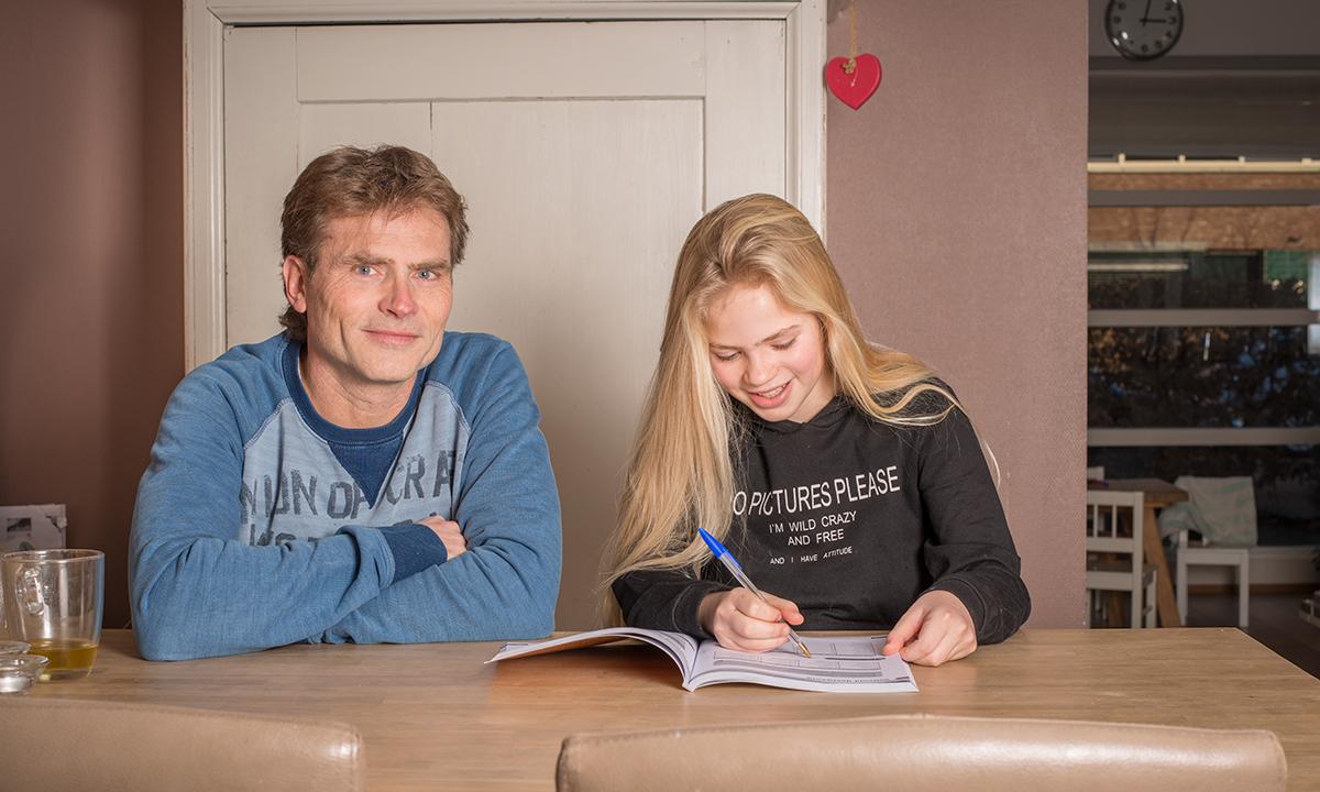 Vader en dochter maken samen huiswerk in werkboek