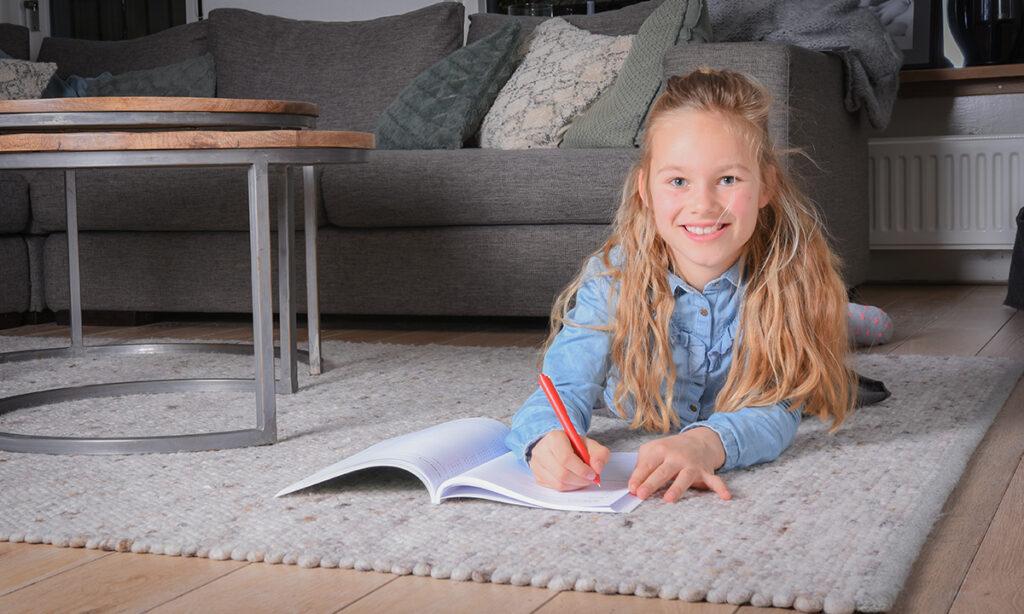 meisje op vloerkleed maakt opdrachten in boek